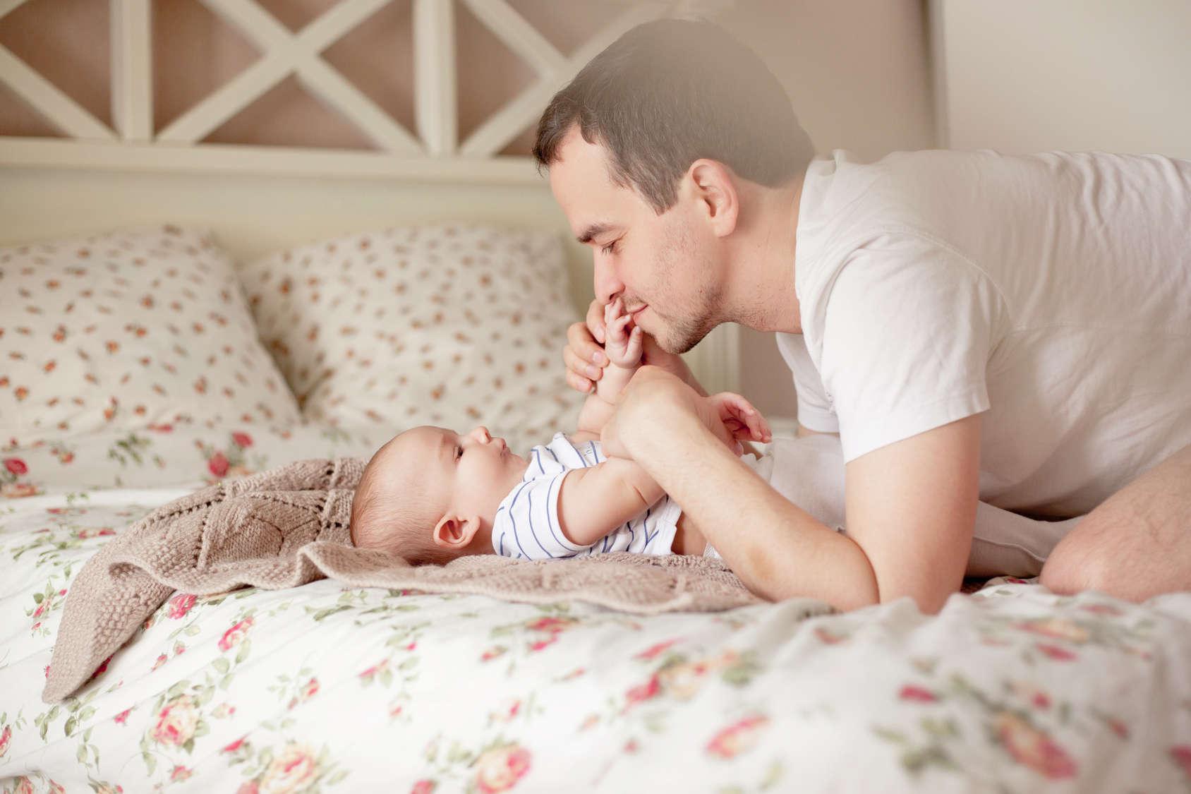 Papa qui embrasse son bébé sur le lit